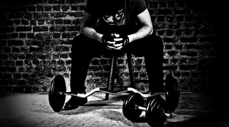 Repos d'un sportif devant une barre de musculation