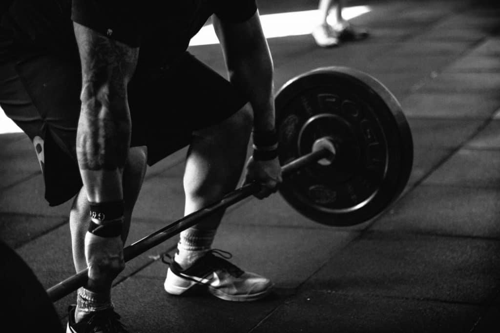 Un homme avec une barre de musculation à ses pieds