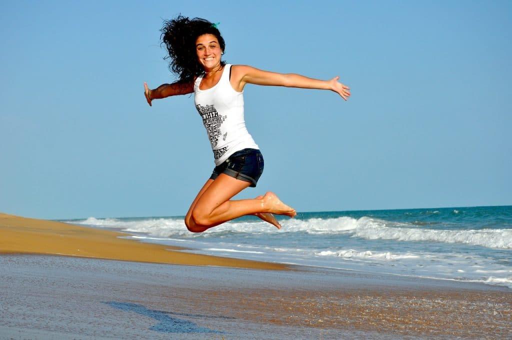 Une femme heureuse qui saute sur une plage