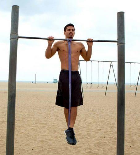 Un sportif qui s'aide d'élastique de musculation pour réaliser des tractions