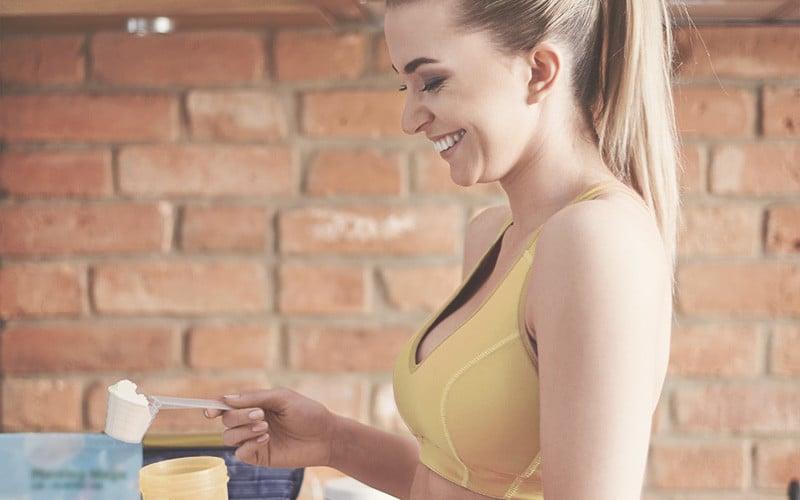 Une femme sportive qui prépare la poudre protéinée dans son shaker de Whey