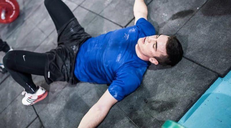 Un sportif épuisait qui est allongé sur le dos pour récupérer après un WOD