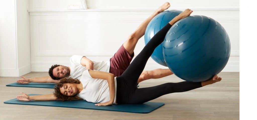 Un couple avec deux ballons de pilates en plein exercice