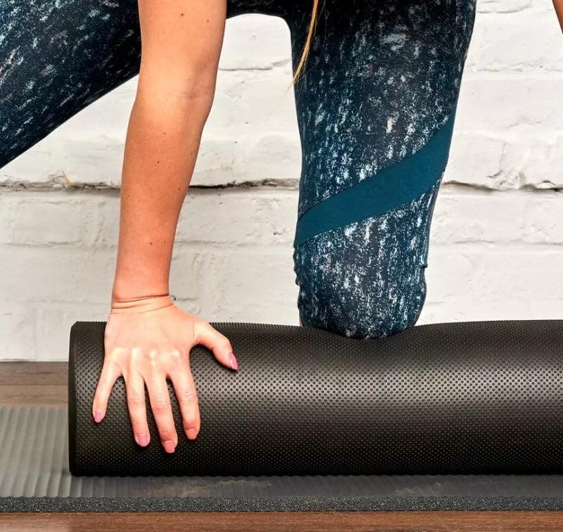 Une femme qui utilise un Foam Roller pour la pratique du Pilates